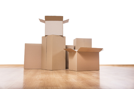 Empty room with a white wall and moving boxes on the floor. Standard-Bild