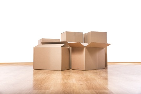 Empty room with a white wall and moving boxes on the floor. 스톡 콘텐츠