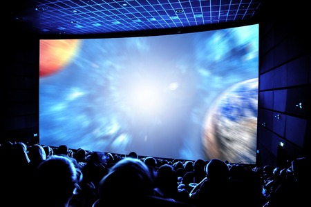 back screen: Cinema. The audience in 3D glasses watching a movie. Elements of this image furnished by NASA.
