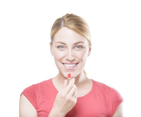 applying lipstick: Attractive blonde woman applying lipstick looking at camera.