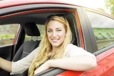 new motor car: Pretty blonde woman driving a red car.