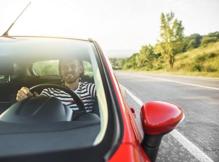 hombre conduciendo: Feliz el hombre que sonríe en controlador nuevo coche rojo en la carretera.
