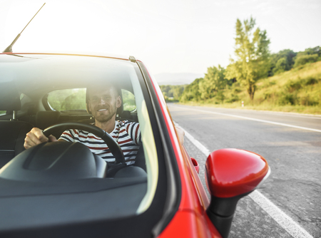 Happy smiling driver man in new red car on the road.
