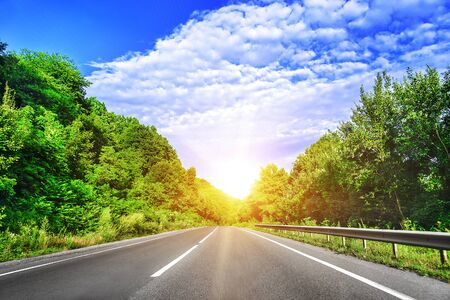 country highway: Country highway in the summer rays of sunset. Stock Photo