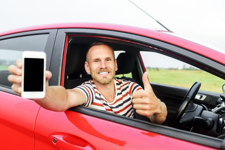 phone message: Man in car showing smart phone display smiling happy. Focus on mobile phone. Stock Photo