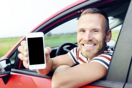 Man in auto met smart phone scherm glimlachen gelukkig. Focus op model. Gestemde foto.