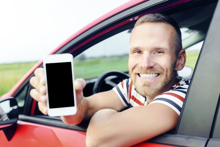 Man in car showing smart phone display smiling happy. Focus on model. Toned photo.