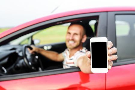 chofer: Hombre en el coche que muestra la pantalla del teléfono inteligente sonriendo feliz. Centrarse en el teléfono móvil. Foto de archivo