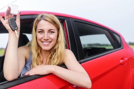 Attractive blonde in a car showing keys. Standard-Bild
