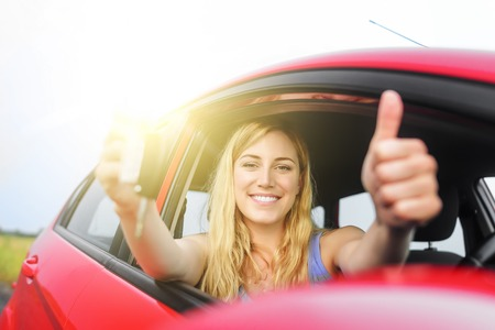 Happy woman in red car showing thumb up and key.