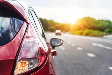 석양 도로에 빨간 자동차입니다. 여행 개념입니다.