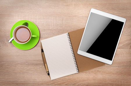 interface design: Tablet PC, notebook and cup of tea on the desktop. Top view.