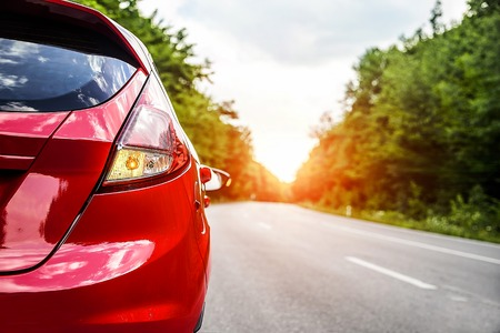 Travel concept. Red car on the road at sunset. Standard-Bild