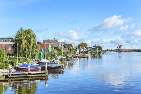 zaandam: Zaanse Schans. Picturesque view of a Dutch village with old windmills and boats located at the river.