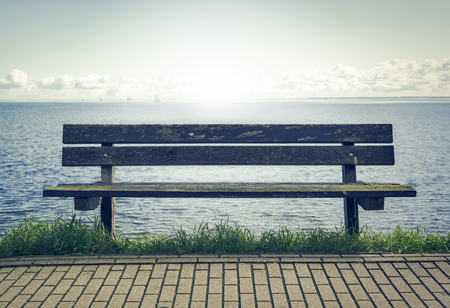 empty bench: Empty bench on the seafront. Toned photo. Stock Photo