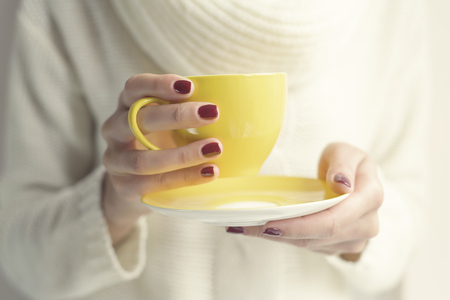 drinking: Cup with a hot drink in female hands close up. Soft style toned photo.