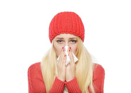 nariz: Goteo nasal de la chica en ropa de invierno. Aislado en blanco.