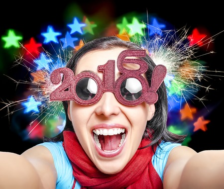 sweet smile: Two thousand and sixteen. Girl in glasses taking selfie. New Years concept.