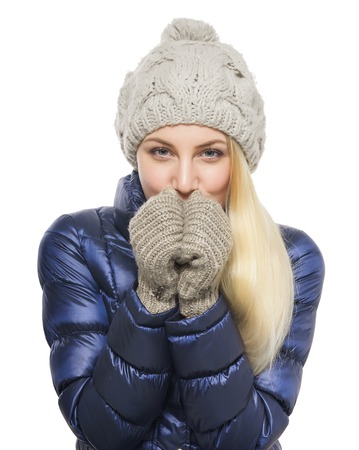 Portrait of cute blonde woman in winter clothes warming hands her breath. Isolated on white background. Standard-Bild