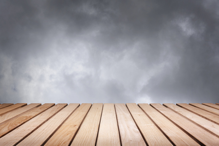 inclement: Wood platform and cloudy dark dramatic sky.