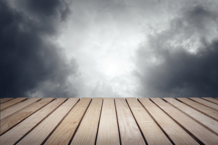 inclement weather: Wood platform and cloudy dark dramatic sky.