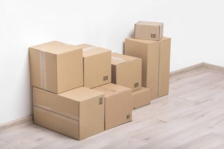 unbranded: Empty room with a white wall and cardboard boxes with unbranded barcode on the floor.