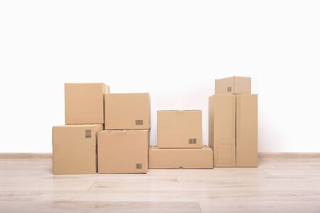 downsize: Empty room with a white wall and cardboard boxes with unbranded barcode on the floor.