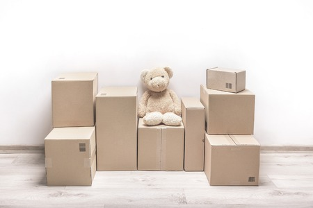 unbranded: Empty room with a white wall and cardboard boxes with unbranded barcode and teddy bear on the floor. Stock Photo