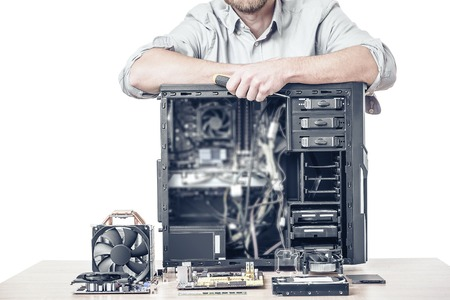 maintenance man: Computer repair concept. Master of computer repair put his hands on the disassembled computer system unit. Toned photo.