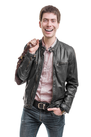 beg: Young man in leather jacket holding beg and smiling. Stock Photo