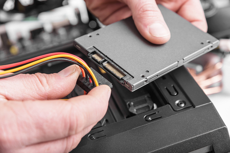repair computer: Connect the SSD hard drive to the computer. Stock Photo