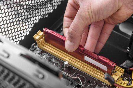 semiconductor: Computer memory installation. Mans hand installs memory in the computer. Stock Photo