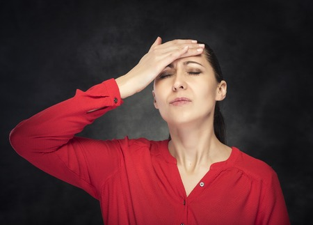 experiencing: Woman experiencing a headache. On a dark background.