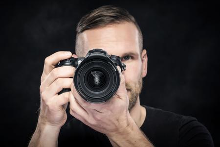 darck: Photographer man with camera on darck background. Focus on camera.