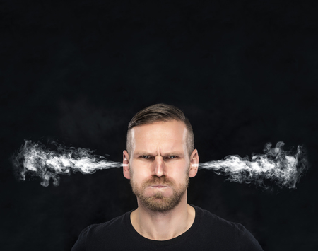 Hombre enojado con el humo o humo que sale de las orejas sobre un fondo oscuro.