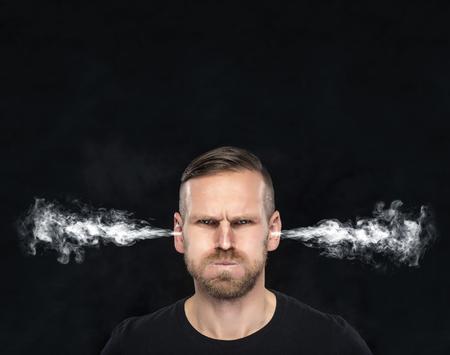 personas enojadas: Hombre enojado con el humo o humo que sale de las orejas sobre un fondo oscuro. Foto de archivo