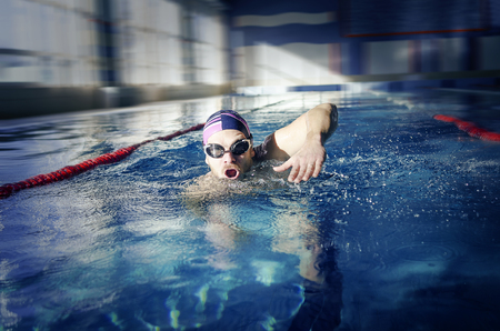 dynamically: Swimmer. Man swims in the pool dynamically.