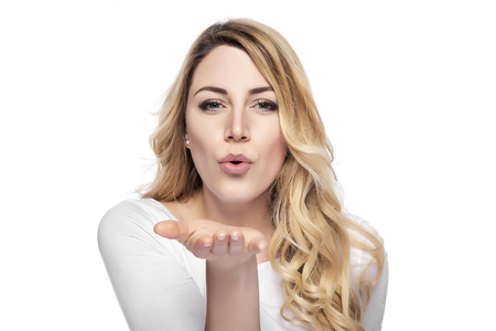白い背景の上の空気キスを送信する金髪の女性 写真素材