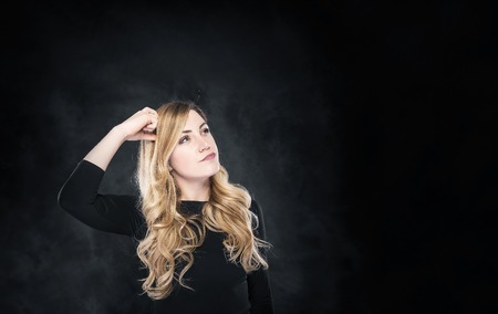 free thinking: Thinking blond woman on a dark background. Free space for your text or image. Stock Photo