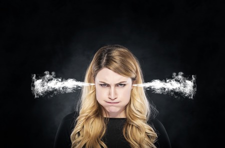 aggravated: Steam or smoke from the ears of the woman over dark background. Stock Photo