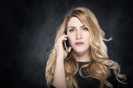 Woman calling with a cell phone over dark background.