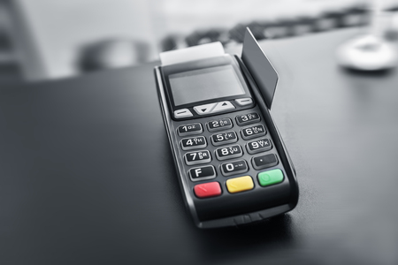 bank withdrawal: Bank terminal and payment card in the office interior.