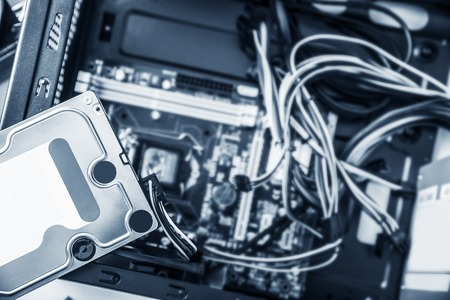 hard drive crash: Hard disk drive HDD on top of the open system unit. Computer repair concept. Toned photo. Stock Photo