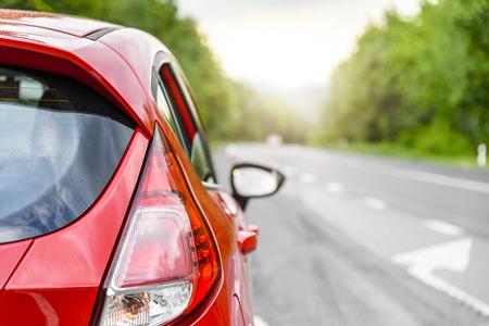 Voiture rouge sur la route au coucher du soleil.