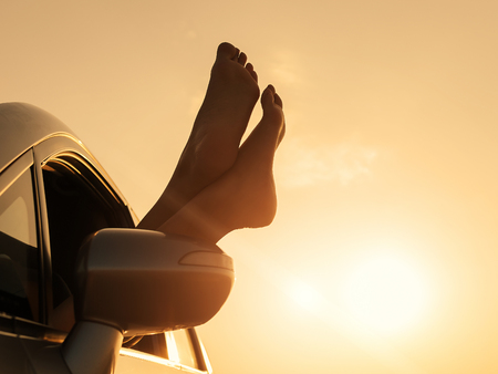 vehicle window: Silhouette of female feet hanging out of vehicle window at sunset. Woman relaxing in a car on road trip.