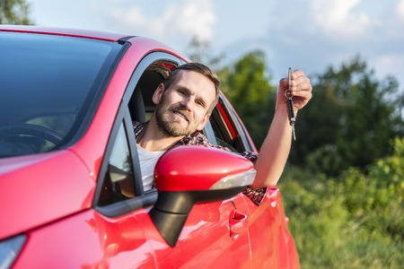 show window: Man Sitting In A Car Outdoors and Showing New Car Keys.