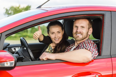 car driving: Two young smiling people in a red car. Girl showing thumbs up. Stock Photo