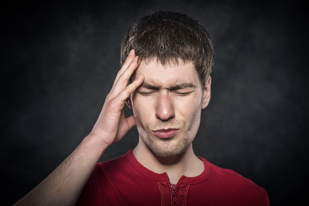 intensely: Young man holding his head feeling a headache or intensely thinking.