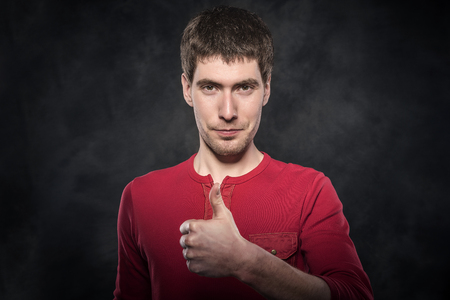 darck: Young man shows thumbs up over darck background. Stock Photo