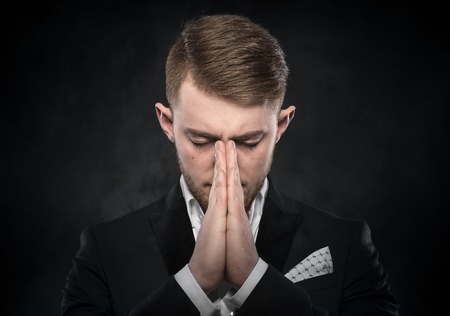 unhappy man: Portrait of businessman praying or thinking over dark background. Stock Photo